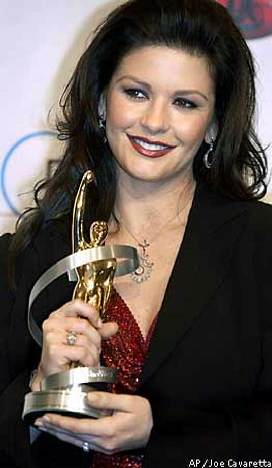 Catherine Zeta-Jones holds her award for supporting actress of the year Thursday, March 6, 2003 backstage at the awards at the Paris Hotel in Las Vegas. (AP Photo/Joe Cavaretta) Photo: JOE CAVARETTA