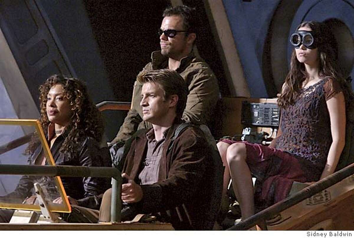 Writer/Director Joss Whedon makes his feature film directorial debut with the futuristic action-adventure Serenity. From left to right are some of the crew of the Serenity, a transport-for-hire ship caught between warring forces out to dominate the galaxy: GINA TORRES as Zoe, NATHAN FILLION as Captain Malcolm Reynolds, ADAM BALDWIN as Jayne and SUMMER GLAU as River. Photo Credit: Sidney Baldwin