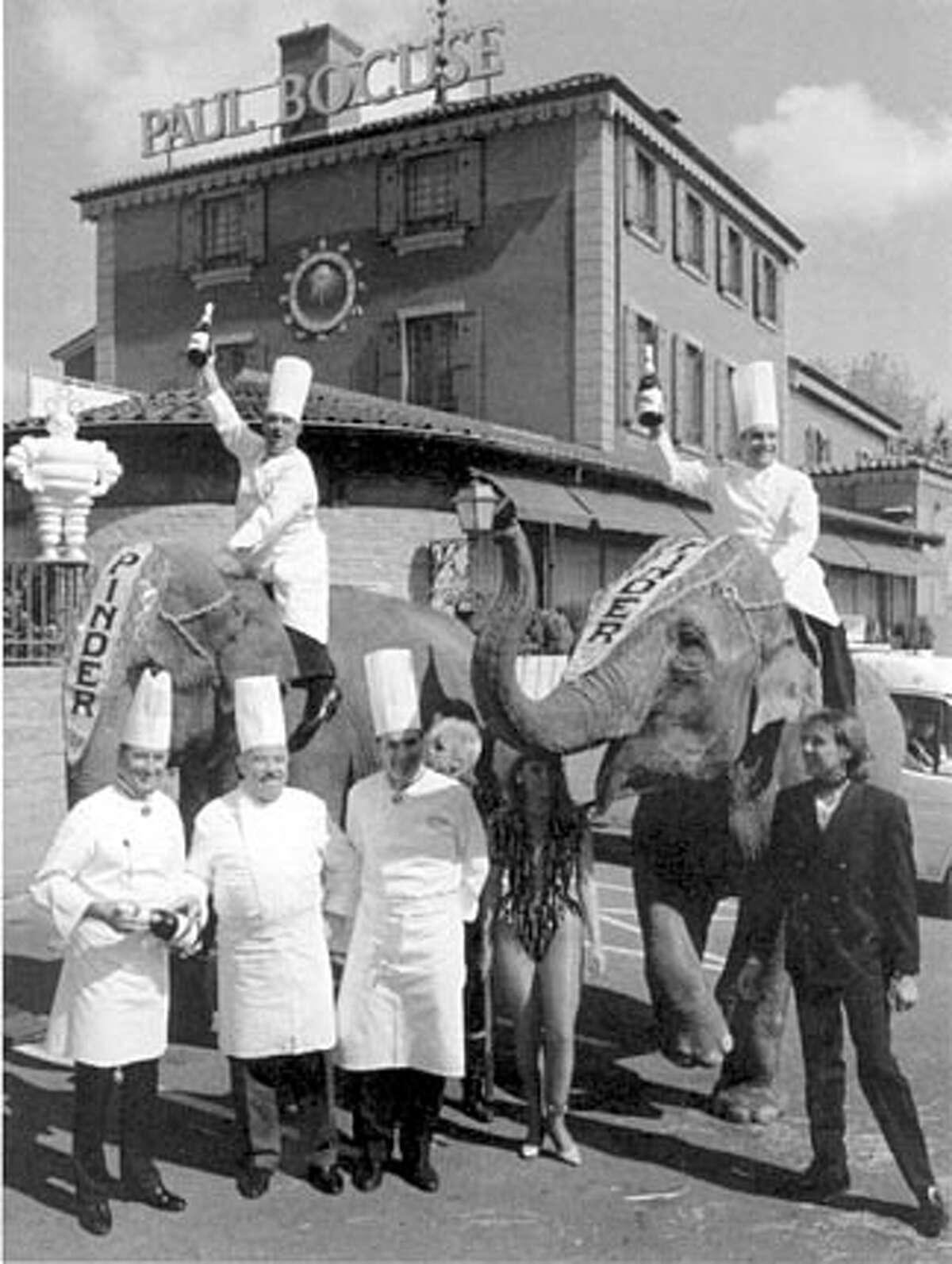 Bernard Loiseau (right elephant) and Paul Bouise (left elephant) celebrate Loiseau's winning a third Michelin star.