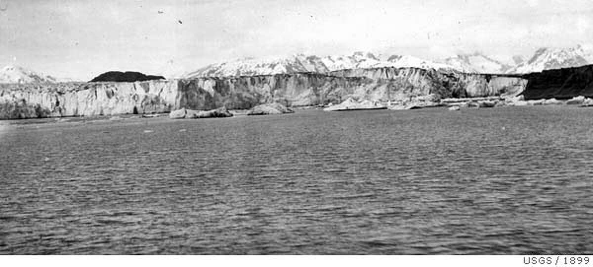 Event on 6/1899 in Alaska. Pair USGS-12 A pair of northeast-looking photographs, both taken from the same shoreline location near Muir Point, Muir Inlet, Glacier Bay National Park and Preserve, Alaska, that document changes that have occurred during the 104 years between June 1899 and September 2003. The 1899 photograph shows the calving terminus of Muir Glacier, near its confluence with Adams Glacier. No vegetation is visible (USGS Photo Library Photograph - Gilbert 278). The 2003 photograph documents the disappearance of Muir and Adams Glaciers from the field of view. Muir Glacier has retreated more than 25 miles to the north. Note the extensive vegetation that has developed. (2003 NPS Photograph by Karpilo).