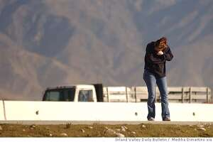 Joanna Stidham covers her face as heavy winds blow across the 210 freeway near the Interstate 15 interchange Thursday Dec. 16 in Fontana, Calif. Stidham came to check the status of her trailer that was toppled over by the winds earlier in the morning. (AP Photo/Inland Valley Daily Bulletin, Mediha Dimartino)**MANDATORY CREDIT**