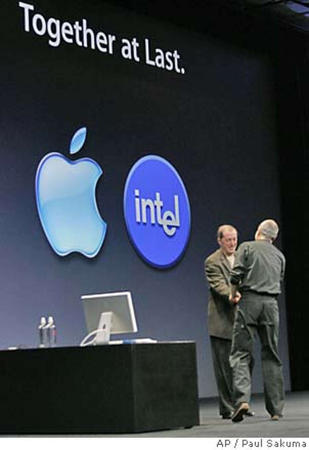Apple Computer Inc. CEO Steve Jobs, right, shake hands with Intel Corp. CEO Paul Otellini, left, at Apples Worldwide Developers Conference in San Francisco, Monday, June 6, 2005. Apple announced it will discontinue using microprocessor chips made by IBM in favor of Intel chips. (AP Photo/Paul Sakuma)