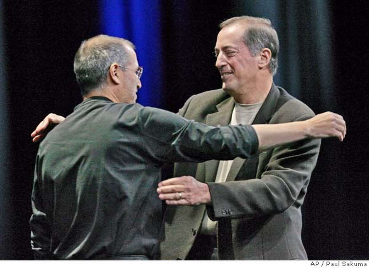 Apple Computer Inc. CEO Steve Jobs, left, hugs Intel Corp. CEO Paul Otellini, right, at Apples Worldwide Developers Conference in San Francisco, Monday, June 6, 2005. Apple announced it will discontinue using microprocessor chips made by IBM in favor of Intel chips. (AP Photo/Paul Sakuma)