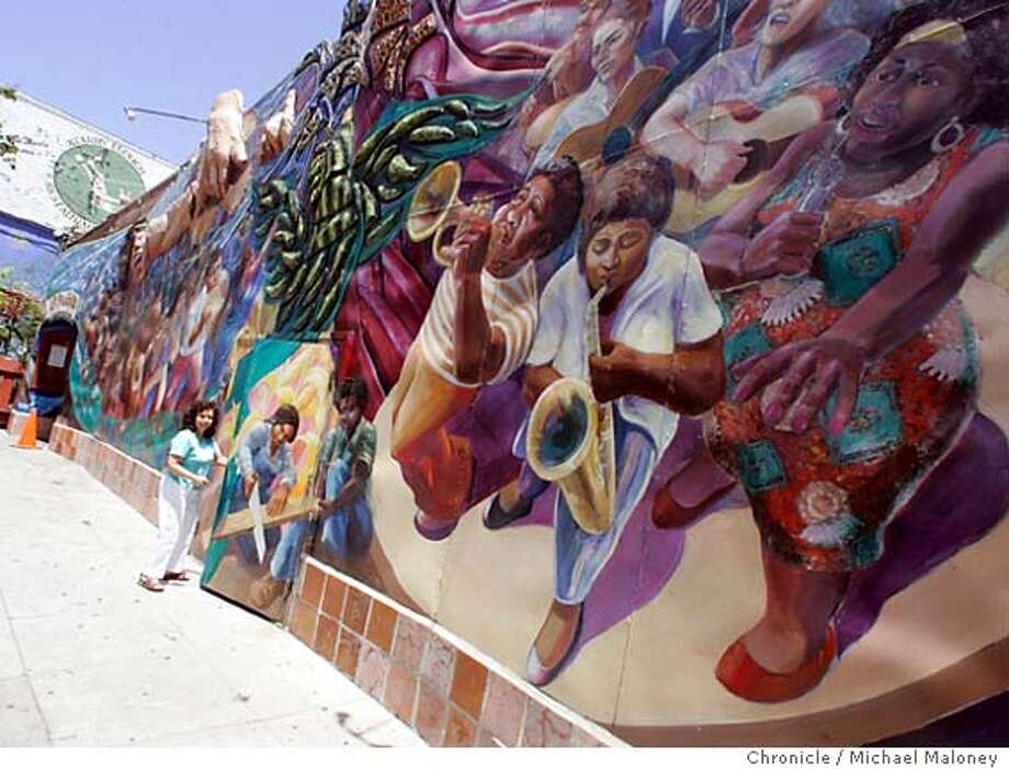 "Laura Ruiz, staff member of the La Pe�a Cultural Center enters the brightly painted building on Shattuck Ave. The mural is titled : La Cancion de la Unidad (Song of Unity).  Berkeley's La Pe�a Cultural Center, started in 1975 in response to the overthrow of Chilean President Salvador Allende, will celebrate its 30th anniversary Saturday with a street fair. The center has a restaurant, cultural events five nights a week, and offers space for non-profit organizations and advocacy groups of many stripes. Founder Eric Leenson went on to start what is today a $700 million ""socially responsible'' investment fund.  Photo by Michael Maloney / San Francisco Chronicle Photo: Michael Maloney"