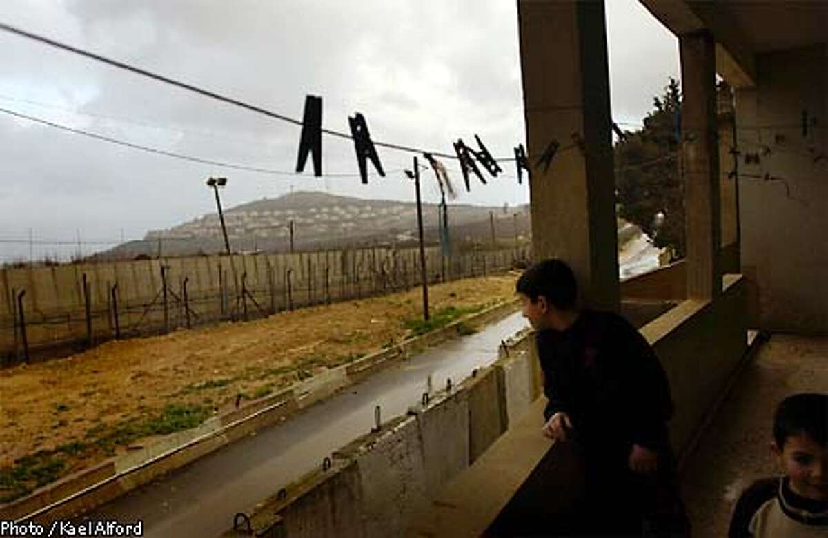 """Lebanese boys play on the balcony of their home in Kfar Kila, Lebanon overlooking a strategically located Israeli town on the UN designated """"blue line"""" border with Israel. South Lebanon was occupied by Israeli forces until May 2000. O3 March 2003 Photo: Kael Alford"""