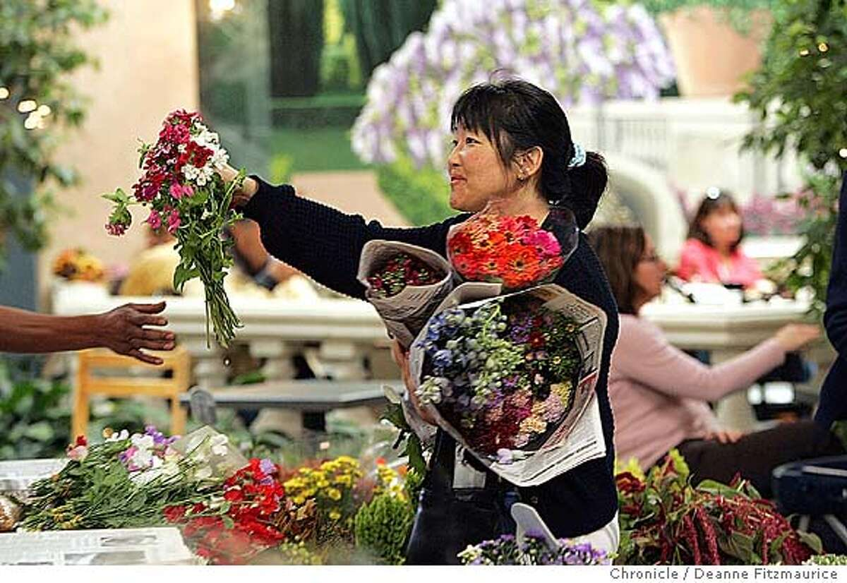 Shirley Phelan, from El Granada, purchases an assortment of flowers from Repettios. The Half Moon Bay Coastal Flower Market is on the third Saturday of every month. Deanne Fitzmaurice / The Chronicle