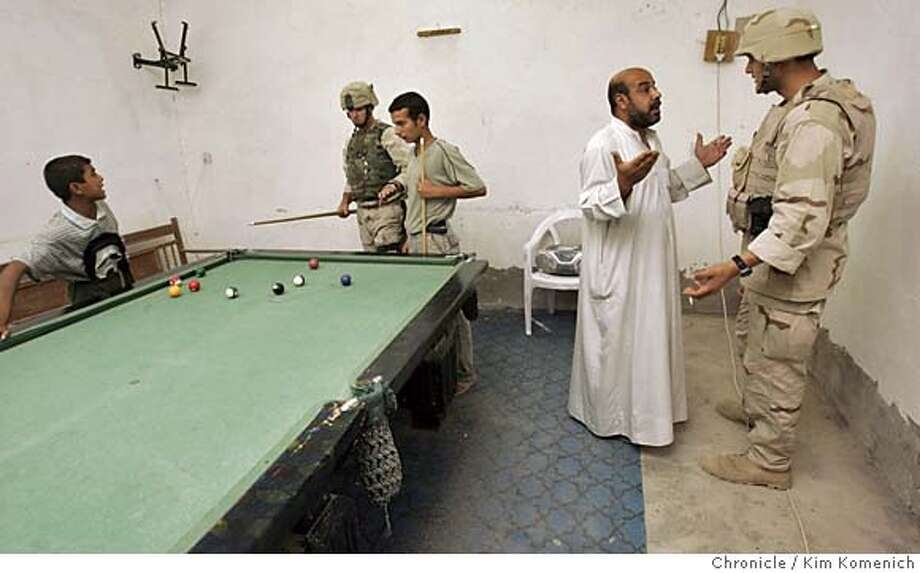 IRAQ08_TIKRIT_KK_202.jpg  Staff Sgt. Kenneth Smith shoots pool with patrons while interpreter Omar Elmenshawi speaks with pool hall owner Saadi Rahim.  We spend a night on the town in Tikrit, Iraq with Lt. Col. Todd Wood and an armed escort of three humvees. Lt. Col Wood walks the streets, shaking hands with merchants. He then buys some clothing. As the evening winds down, members of his escort play pool with Tikrit ersidents at a local pool room. San Francisco Chronicle photo by Kim Komenich Photo: Kim Komenich
