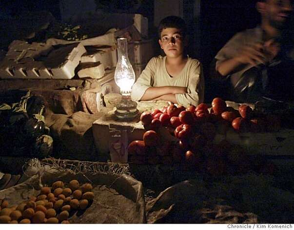 Abdullah Ahmer watches his father's fruit stand while his father and others talk with Lt. Col. Wood.  We spend a night on the town in Tikrit, Iraq with Lt. Col. Todd Wood and an armed escort of three humvees. Lt. Col Wood walks the streets, shaking hands with merchants. He then buys some clothing. As the evening winds down, members of his escort play pool with Tikrit ersidents at a local pool room. San Francisco Chronicle photo by Kim Komenich Photo: Kim Komenich
