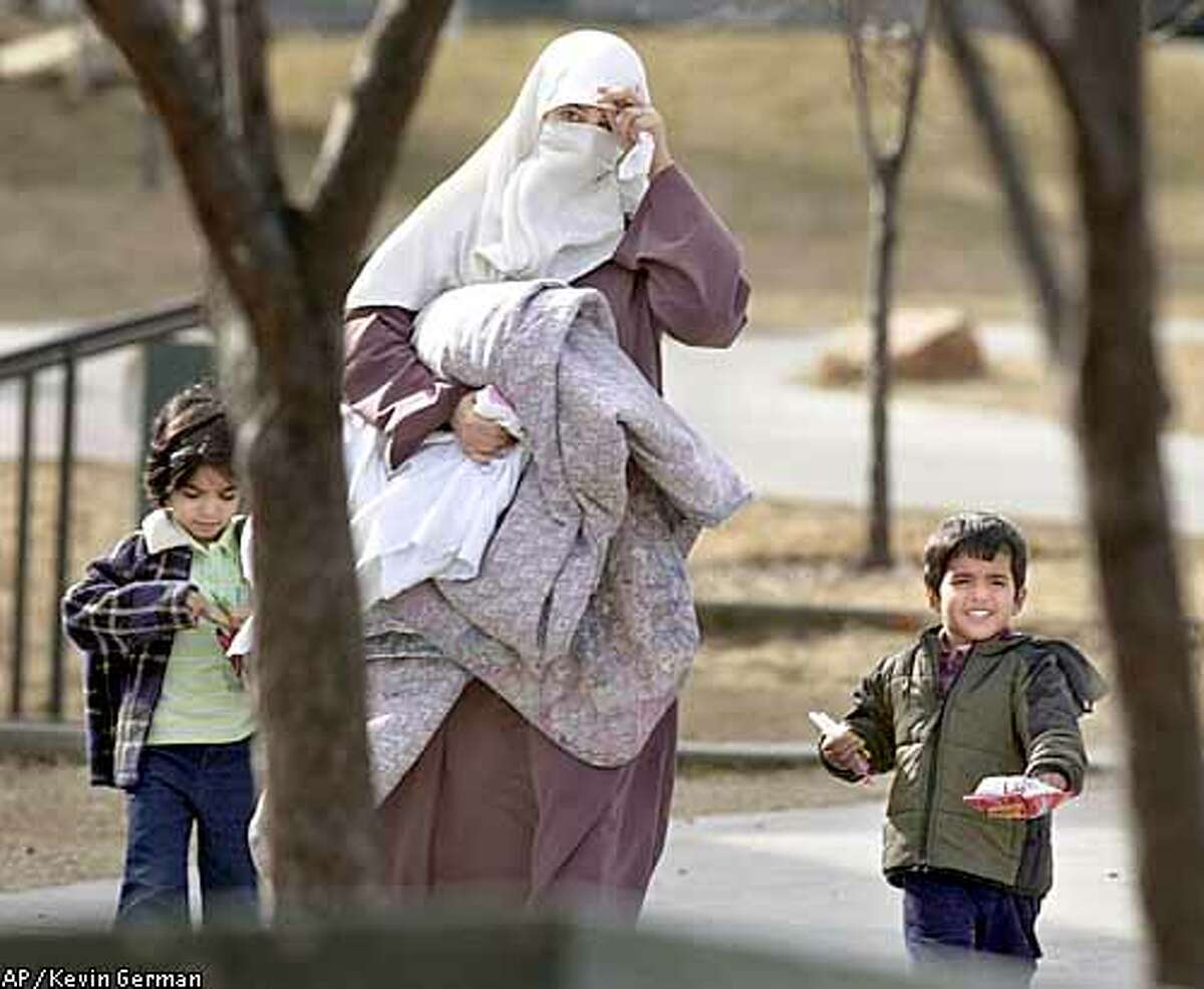 Persons identified by the FBI as being the wife, center, and children of University of Idaho student Sami Omar Al-Hussayen, walk through their apartment complex while government agents search the family's home in Moscow, Idaho, Wednesday, Feb. 26, 2003. University of Idaho officials said Thursday, Feb. 27, 2003, they will be flexible in deciding whether the family of Sami Omar Al-Hussayen can remain in campus housing while the graduate student faces terrorism-related charges. (AP Photo/Kevin German)