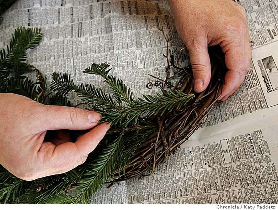 "NBWREATHMAKING_rad.jpg Dawn Yun of San Rafael conducts a ""how to"" on making holiday wreaths. SHOWN: Step One--insert branches of greenery into the wreath form (this one's made of grape vines) to form a nice base for decorations. Katy Raddatz / The Chronicle Photo: Katy Raddatz"