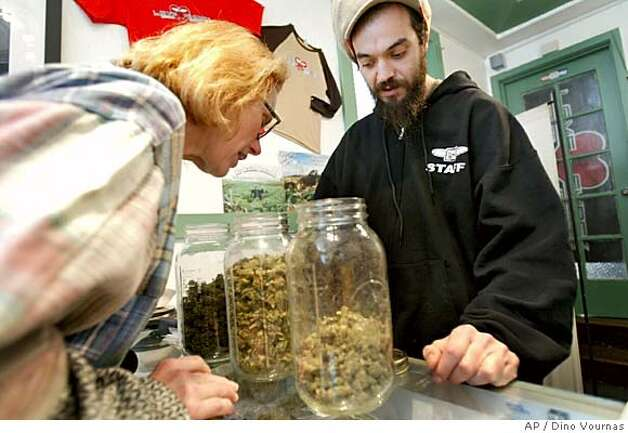 An unidentified medical marijuana patient, assisted by volunteer Adolfo Comunale, right, as she smells the different offerings of the Love Shack medicinal cannabis shop, in the Mission District of San Francisco, Monday, June 6, 2005 . It was business as usual in the medical marijuana shops in the wake of the Supreme Court ruled that people who smoke marijuana because their doctors recommend it to ease pain can be prosecuted for violating federal drug laws, overriding medical marijuana statutes in 10 states. (AP Photo/Dino Vournas) Photo: DINO VOURNAS