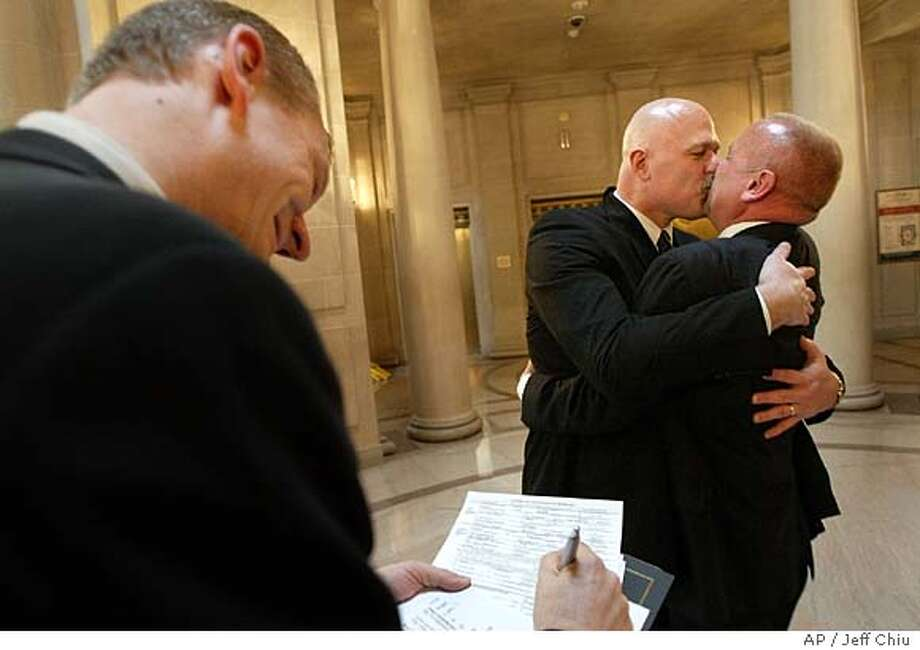 **FOR USE AS DESIRED WITH YEAR-END STORIES - FILE** Rich Walker, center, kisses Brad Chilcoat after the couple was married by Deputy Marriage Commissioner D.J. Dull, left, at City Hall in San Francisco in this Feb. 15, 2004 file photo. (AP Photo/Jeff Chiu, File) FOR USE AS DESIRED WITH YEAR-END STORIES. FEB. 15, 2004 FILE PHOTO Photo: JEFF CHIU