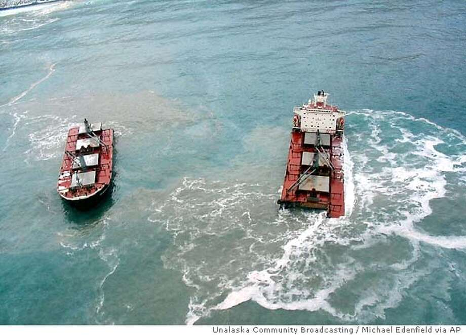 The two halfs of the Malaysian cargo ship Selendang Ayu, in this photo released by Unalaska Community Broadcasting, sits about 400-500 yards offshore in Skan Bay on Unalaska Island near Unalaska, Alaska in the Aleutian Island chain, about 800 air miles southwest of Anchorage Thursday Dec. 9, 2004. A Coast Guard cutter and three tug boats were unable to halt the 738 feet freighter's approach to shore after its engines quit. The ship later ran aground and split apart Wednesday night. A Coast Guard helicopter crashed into the Bering Sea with 10 people aboard while conducting a rescue of the freighter crew. Four of the 10 were picked up by another helicopter participating in the rescue, the Coast Guard said. Rescuers continued searching for the remaining six Thursday. (AP Photo/Unalaska Community Broadcasting, Michael Edenfield) Photo: MICHAEL EDENFIELD