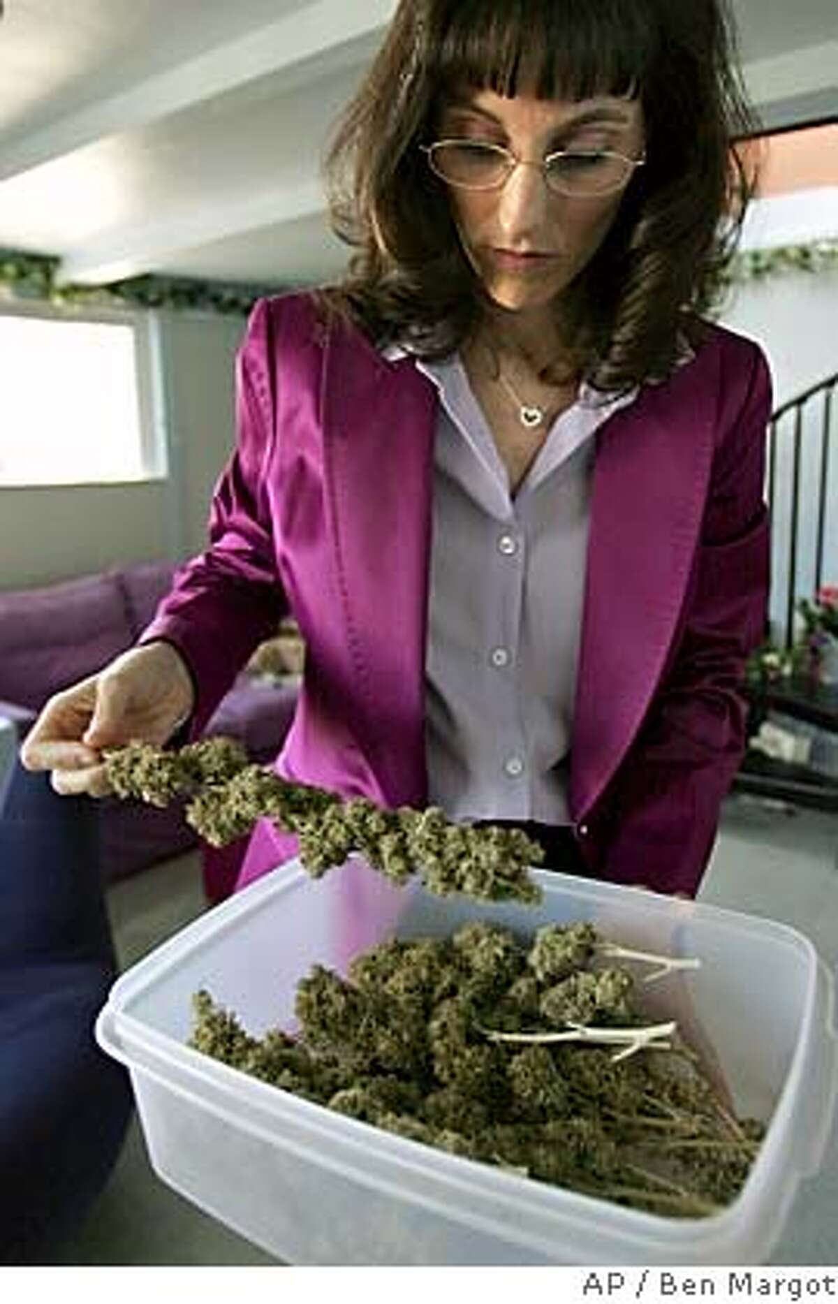 Angel Raich is seen with cannabis buds at her home Monday, June 6, 2005, in Oakland, Calif. Raich is one of two persons that sued then-U.S. Attorney General John Ashcroft, asking for a court order letting them smoke, grow or obtain marijuana without fear of arrest, home raids or other intrusion by federal authorities. Federal authorities may prosecute sick people whose doctors prescribe marijuana to ease pain, the Supreme Court ruled Monday, June 6, 2005, concluding that state laws don't protect users from a federal ban on the drug. (AP Photo/Ben Margot)