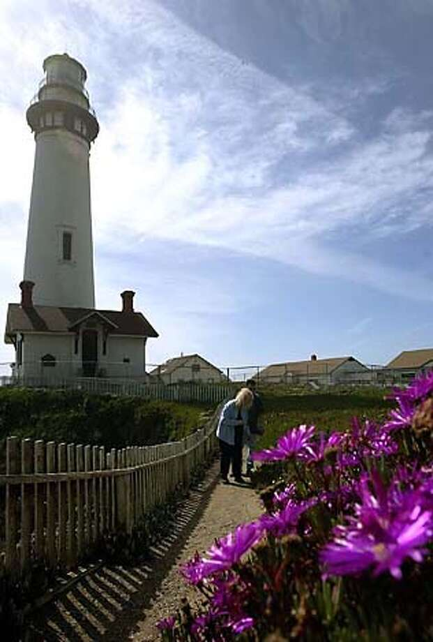 TRAVEL Pescadero -- Dawn and Mark Kemp of Denver walk below the Pigeon Point Lighthouse at Pigeon Point Light Station State Historic Park, south of Half Moon Bay, Calif., Thursday, March 11, 2004. The lighthouse was officially transferred to the state Parks Department, which has been the property's caretaker for 20 years, May 25, 2005. (AP Photo/Jeff Chiu) Photo: JEFF CHIU