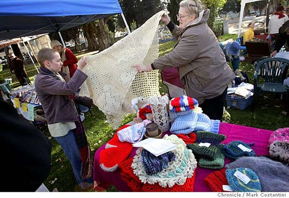 One of the women(name TK, right) shows off her wares to a potential customer.  Three formerly homeless women for months have been knitting items to sell as holiday gifts at the Berkeley Farmers Market. They plan to split the proceeds with the Homeless Action Center. We need shots of them selling and some details of their items. Mark Costantini / The Chronicle Photo: Mark Costantini