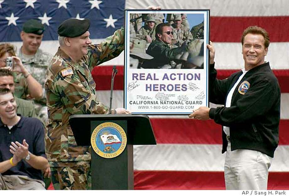 Gov. Arnold Schwarzenegger (right) shows a picture given by Maj. Gen. Thomas Eres (left) during the California National Guard Welcome Home Day held Saturday in Los Alamitos (Orange County). Associated Press photo by Sang H. Park