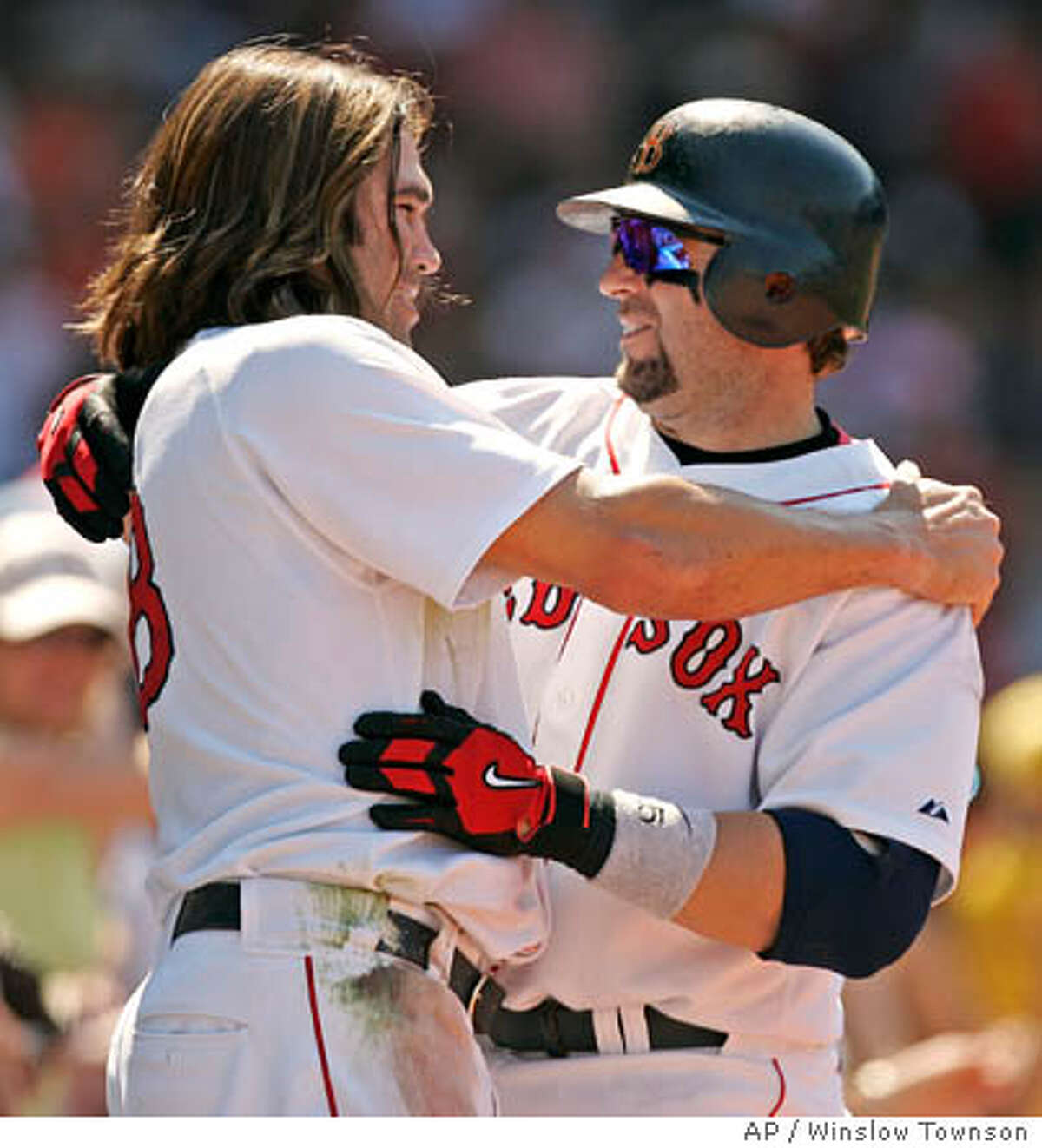 Boston Kevin Millar, right, is congratulated by teammate Johnny Damon after Millar's first of two home runs during the Los Angeles Angels of Anaheim's 13-6 win at Fenway Park in Boston Saturday, June 4, 2005. Millar had three hits and three RBI in the loss. (AP Photo/Winslow Townson)
