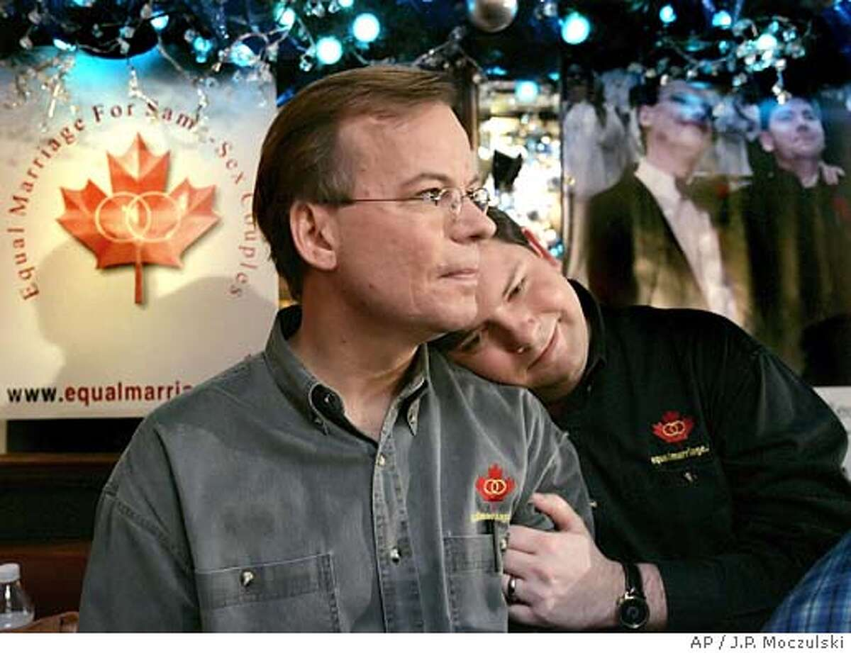 Kevin Bourassa, left, and Joe Varnell, the first North American gay couple to claim to be married, embrace during a celebration of the Supreme Court of Canada opinion affirming the legality of same-sex marriage, at a Toronto bar on Thursday, Dec. 9, 2004. A wedding photo of the couple sits on a wall in the upper right corner of the frame. (AP PHOTO/J.P. Moczulski, AP)