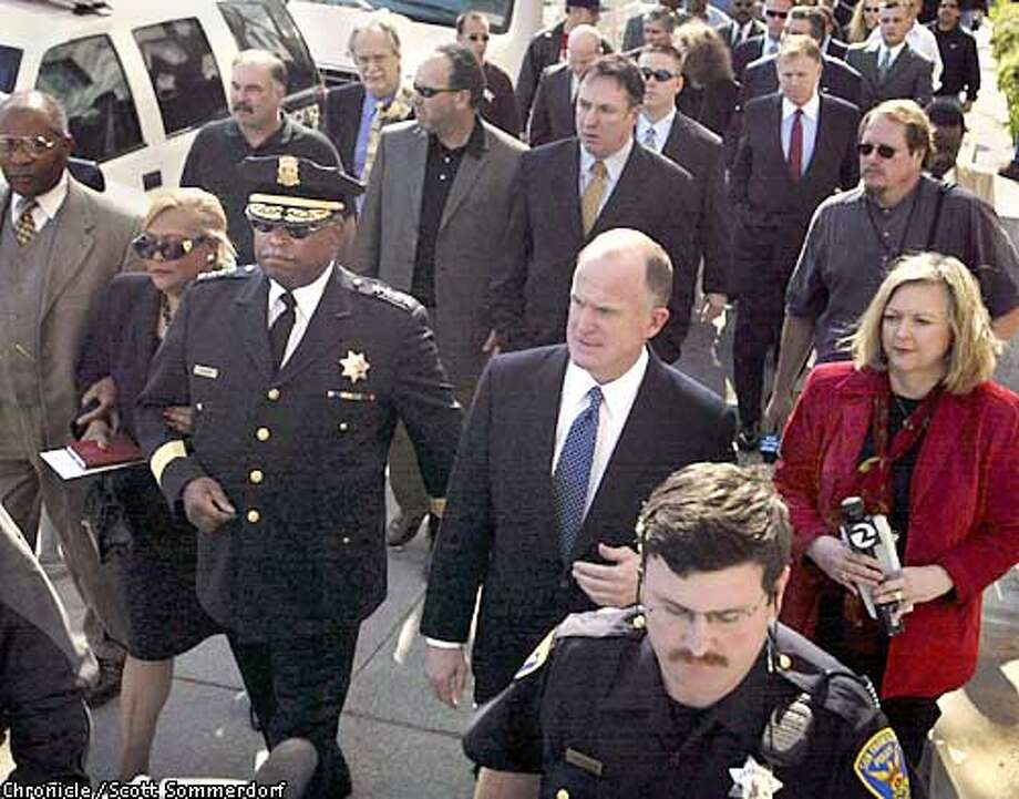 SF Police Chief Earl Sanders with his wife on his arm and Assistant Chief Fagan to his left arrive at the Hall Of Justice Tuesday March 4th, 2003 for their arraignment. (SF CHRONICLE PHOTO BY SCOTT SOMMERDORF) Photo: SCOTT SOMMERDORF