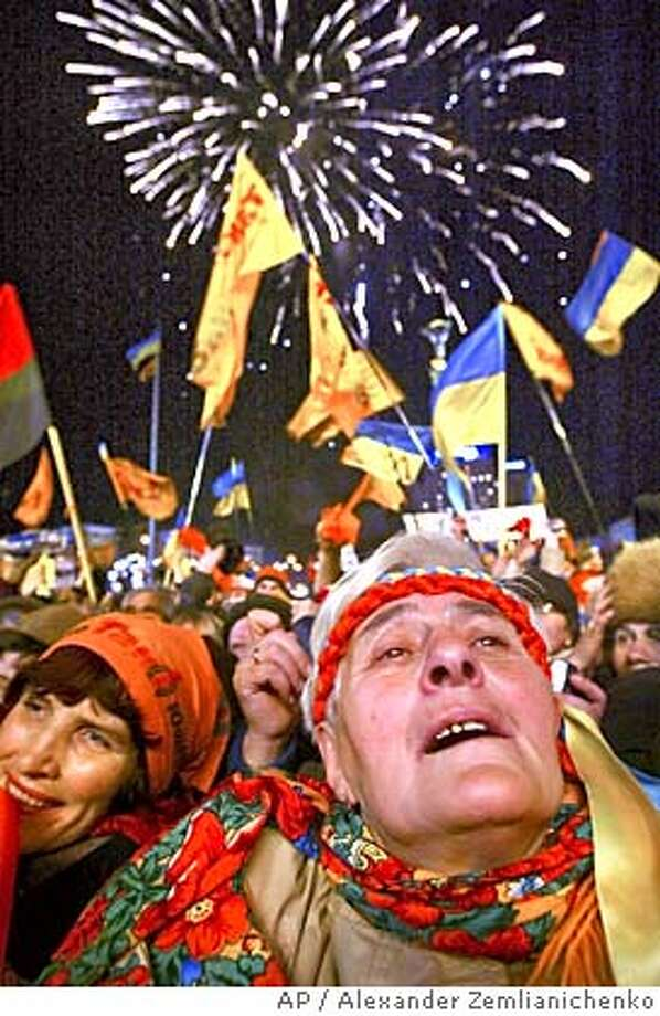 Ukrainians celebrate the parliamentary vote on electoral reforms during a rally at Independence Square in downtown Kiev, Wednesday, Dec. 8, 2004. Ukraine's parliament adopted electoral and constitutional changes Wednesday in a compromise intended to defuse the nation's political crisis touching off thunderous celebrations from opposition supporters.(AP Photo/Alexander Zemlianichenko) Photo: ALEXANDER ZEMLIANICHENKO