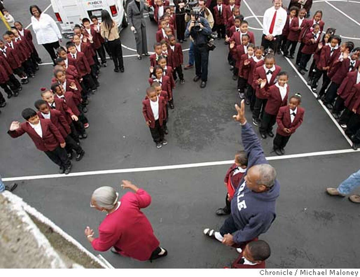 Bill Cosby waves goodbye to the students as he follows principal Louise Jones and holds the hands of student escorts Nita Fanaika (top) and Quintrell Anderson (bottom), both 3rd graders. Months after blasting the African American community for failing to keep their children in school and out of jail, actor/comedian Bill Cosby visited the Bayview-Hunter's Point area on Thursday to tour the Dr. Charles Drew College Preparatory Academy, one of the San Francisco school district's new