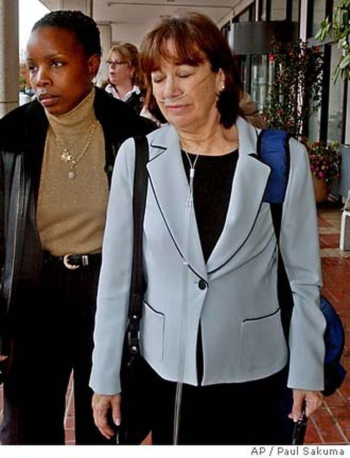Jackie Peterson, right, mother of Scott Peterson, is escorted by police, left, as she leaves a Redwood City, Calif., courthouse, Wednesday, Dec. 8, 2004 after she testified in the penalty phase of Scott Peterson's mrurder trial. Peterson is the Modesto, Calif., man who was convicted of the murder of his wife, . (AP Photo/Paul Sakuma) Photo: PAUL SAKUMA