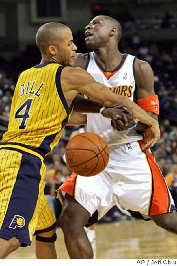 Golden State Warriors' Mickael Pietrus of France is fouled by Indiana Pacers' Eddie Gill during the fourth quarter in Oakland, Calif., on Saturday, Dec. 4, 2004. Pietrus scored 15 points and grabbed six rebounds off the bench as the Warriors won 104-96. (AP Photo/Jeff Chiu) Photo: JEFF CHIU