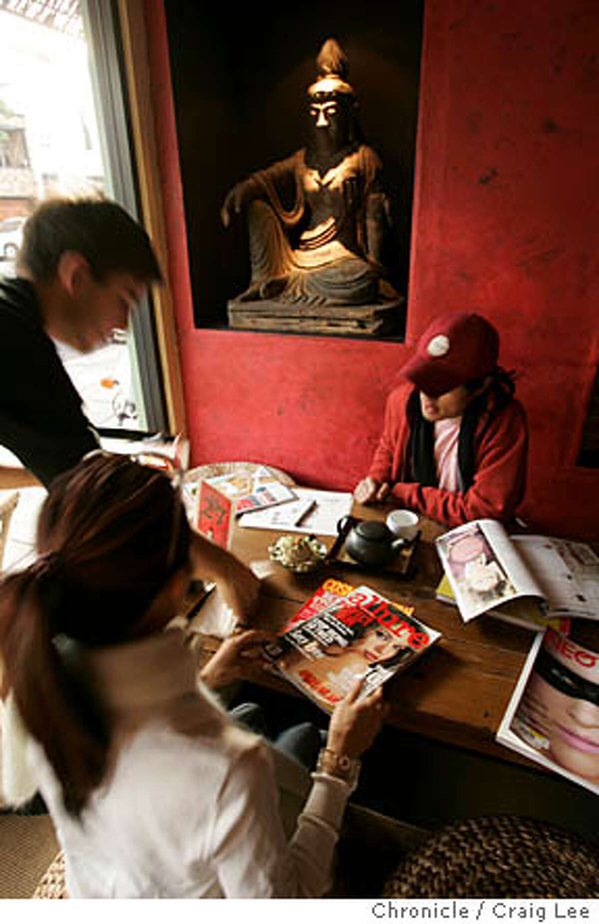 Samovar Tea Lounge at 498 Sanchez street at 18th street. Photo of Adam O'Neill (far left) serving, Linda Pham middle foreground, and Fernando Kabigting. The two are art students looking over magazines while getting some tea. Event on 11/30/04 in San Francisco. Craig Lee / The Chronicle