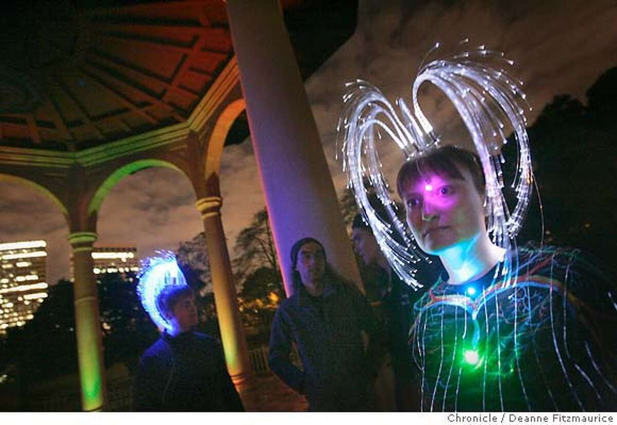 For a Burning Man gathering at Lake Merritt in Oakland, Dawn Ryan shows off a glowing fiber-optic outfit she created and wore at Burning Man. Chronicle photo by Deanne Fitzmaurice