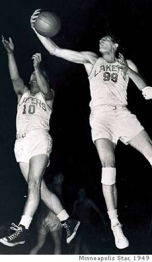 ** FILE ** Minneapolis Lakers' George Mikan, right, grabs a rebound in front of teammate Herman Schaefer during their BAA game against the Washington Capitols in this Jan. 31, 1949 file photo in Minneapolis. Mikan, professional basketball's first dominant big man who led the Minneapolis Lakers to five NBA championships, has died, family members said Thursday, June 2, 2005. He was 80. (AP Photo/Minneapolis Star)