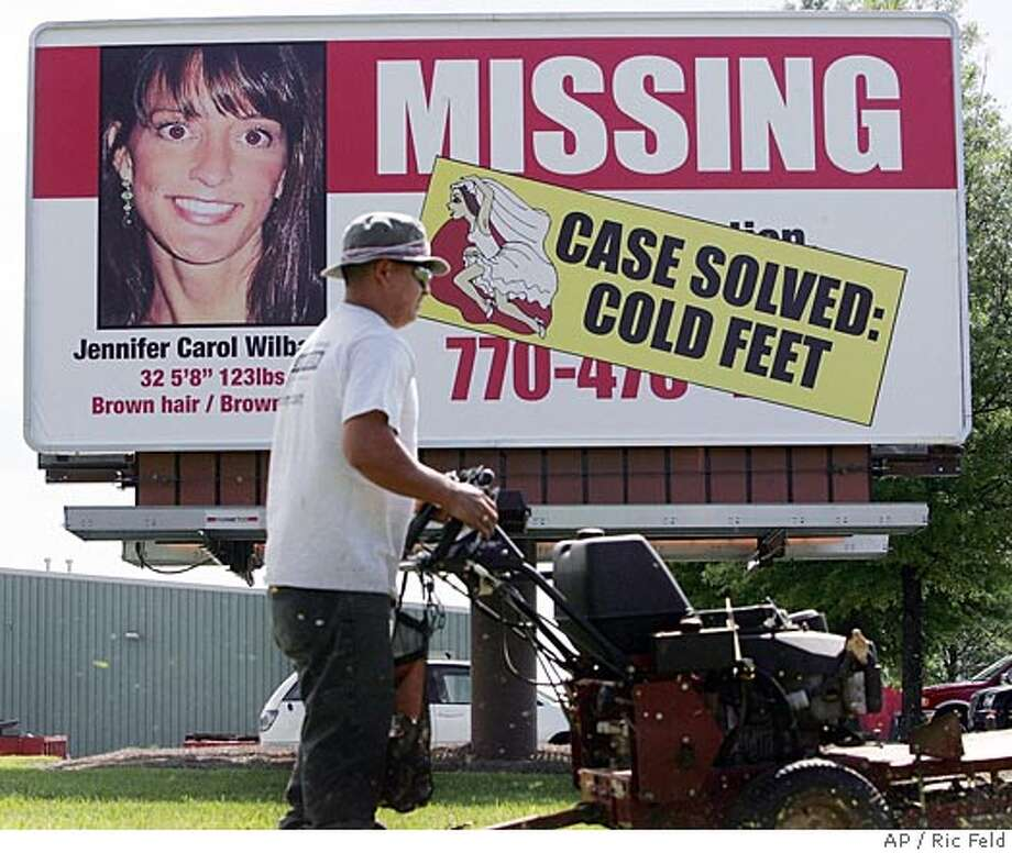 Jose Armando Nino drives his lawnmower past a billboard with the likeness of runaway bride Jennifer Wilbanks in Duluth, Ga., Tuesday, May 3, 2005. Wilbanks, who had vanished Tuesday, April 26 after saying she was going out jogging, initially told authorities she was abducted. But she later admitted she took a cross-country bus trip to Albuquerque, N.M., to avoid her lavish, 600-guest wedding, which was to have taken place Saturday. (AP Photo/Ric Feld) Photo: RIC FELD