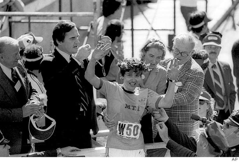 "Rosie Ruiz, of New York, waves to the crowd after receiving the laurel wreath from the wife of Boston's mayor, Katherine White after she was announced as winner of the women's division of the Boston Marathon on April 22, 1980. Turns out Ruiz took a ""short cut"" by riding the city's subway system and was disqualified as the champion. (AP Photo)"