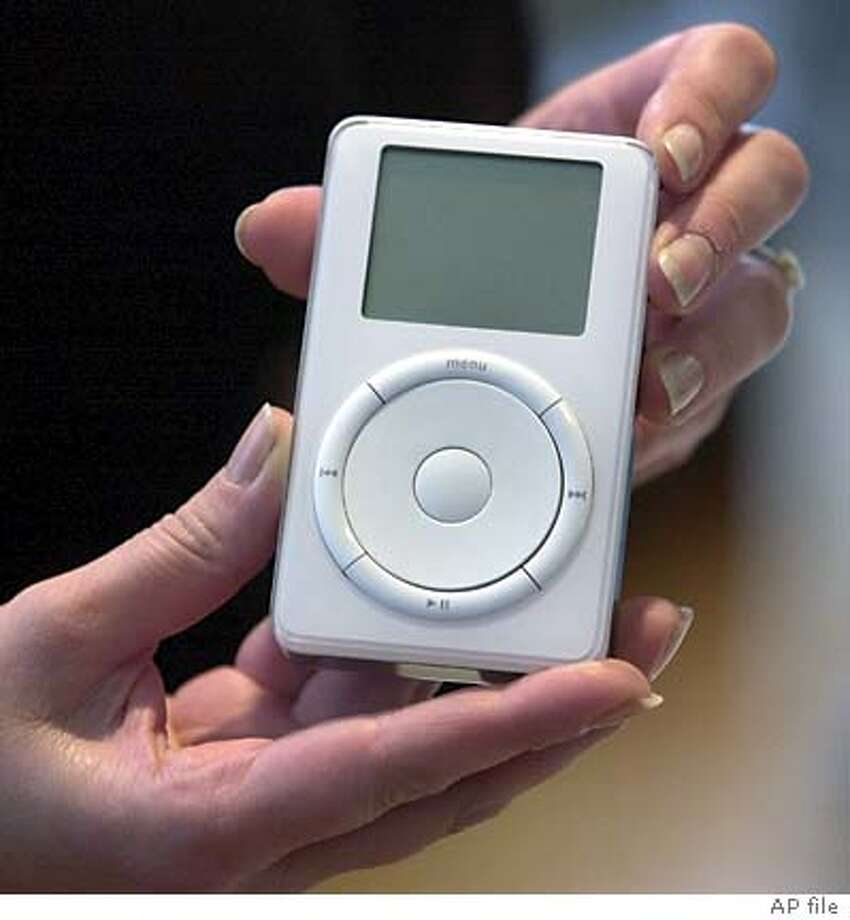 Apple's new digital music player, iPod, is displayed after its introduction by Apple Computer Inc. chief executive officer Steve Jobs during a news conference Tuesday, Oct. 23, 2001 in Cupertino, Calif. Macintosh owners can download 1,000 compact disc quality songs onto the iPod's five gigabyte hard drive in less than 10 minutes. The MP3 player works only on Macintoshes running Apple's proprietary operating systems and iTunes 2, the company's latest music software. (AP Photo/Julie Jacobson) Photo: JULIE JACOBSON