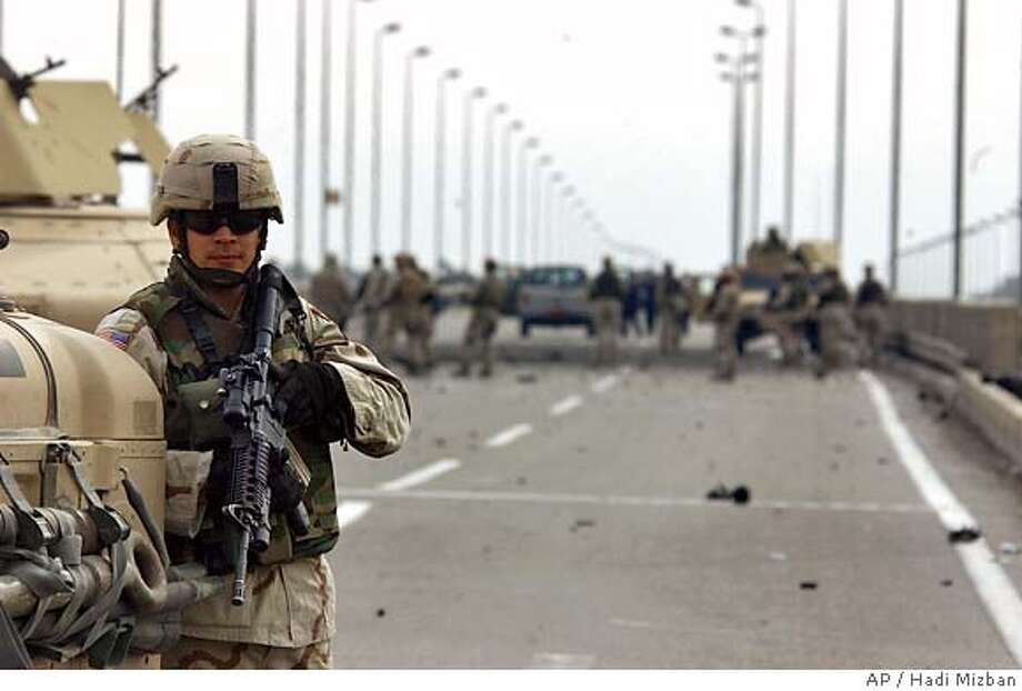 A US soldier guards the site where they have detonated an abandoned car packed with explosives in Baghdad, Iraq, Monday Dec. 6 2004. (AP Photo/Hadi Mizban) Ran on: 12-07-2004  Photo caption Photo: HADI MIZBAN