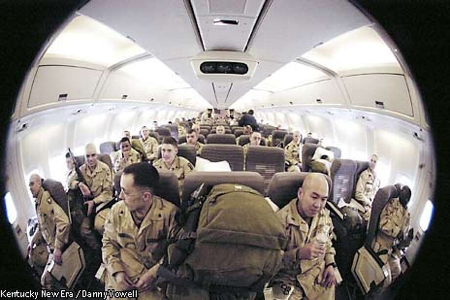 Soldiers from the 101st Airborne Division, shown through a fish-eye lens, wait for takeoff aboard a commercial airliner at Campbell Air Field at Fort Campbell, Ky., en route to the Central Command area of operations in the Persian Gulf, Friday, Feb. 28, 2003. The soldiers are part of a large contingent from Fort Campbell being deployed for a possible war with Iraq. Over 20,000 troops from the division are expected to deploy. (AP Photo/Kentucky New Era / Danny Vowell) Photo: DANNY VOWELL
