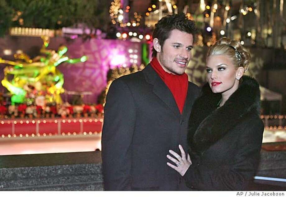 Jessica Simpson, right, and Nick Lachey pose for photographs before the Rockefeller Center Christmas tree lighting ceremony Tuesday, Nov. 30, 2004 in New York. (AP Photo/Julie Jacobson) Datebook#Datebook#Chronicle#12/06/2004#ALL#5star##0422493463 Photo: JULIE JACOBSON