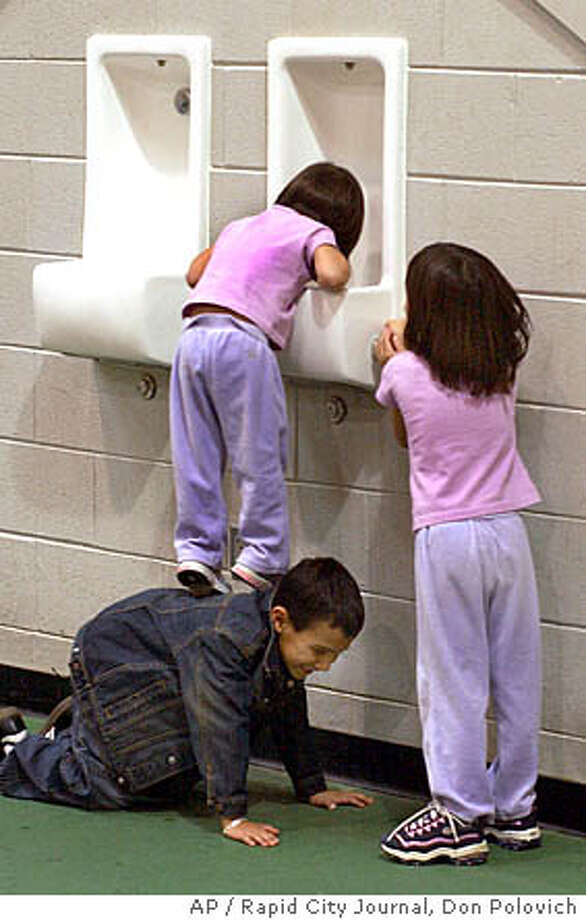 Janaina Janin, 2, drinks from a fountain while being propped by her cousin Isai Rodriguez, 6, and as her sister Joana, 5, right, turns on the water, Saturday, Dec. 4, 2004, during an indoor soccer tournament in Spearfish, S.D. (AP Photo/Rapid City Journal, Don Polovich) Photo: DON POLOVICH