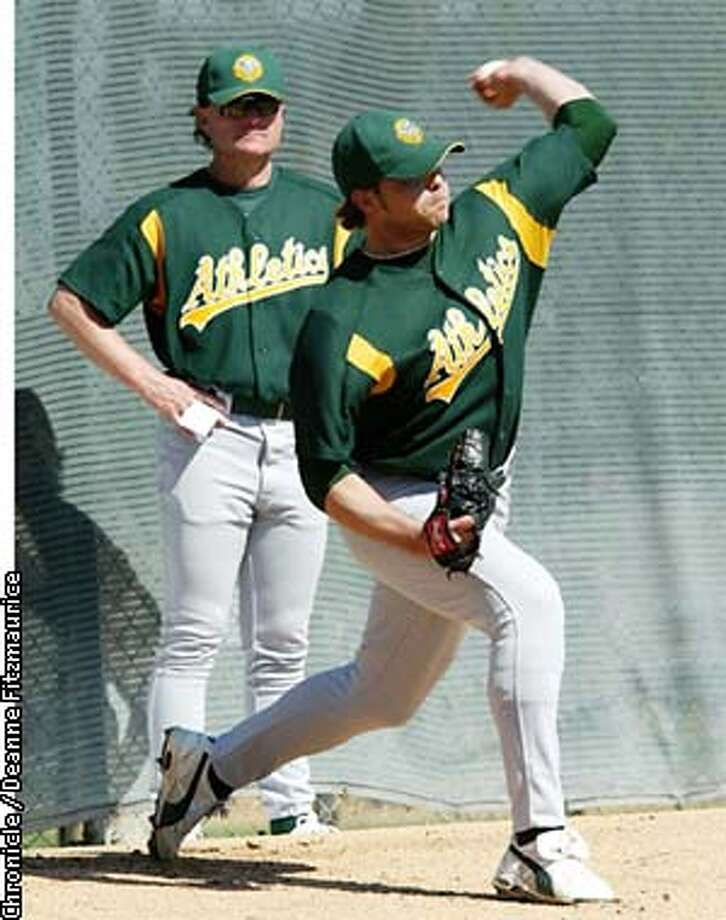 THLETICS1-C-25FEB03-SP-DF John Rheinecker, left-handed pitcher throws pitches at the Oakland Athletics spring training at Phoenix, Arizona. Watching closely is Rick Peterson, pitching coach. CHRONICLE PHOTO BY DEANNE FITZMAURICE