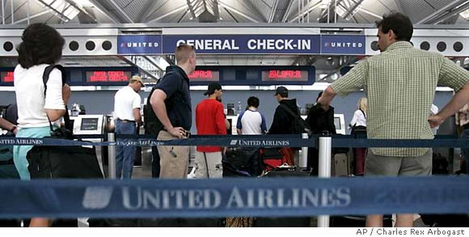 Passengers wait to check in for their United Airline flights at Chicago's O'Hare International Airport in Chicago, Tuesday, May 31, 2005. ' mechanics union ratified a five-year contract Tuesday, removing one strike threat from the carrier as another labor group negotiated down to the deadline. A majority of the 7,000 members of the Aircraft Mechanics Fraternal Association voted to accept a five-year pact entailing $96 million in annual reductions and 3.9 percent pay cuts, among other conditions. (AP Photo/Charles Rex Arbogast) Photo: CHARLES REX ARBOGAST