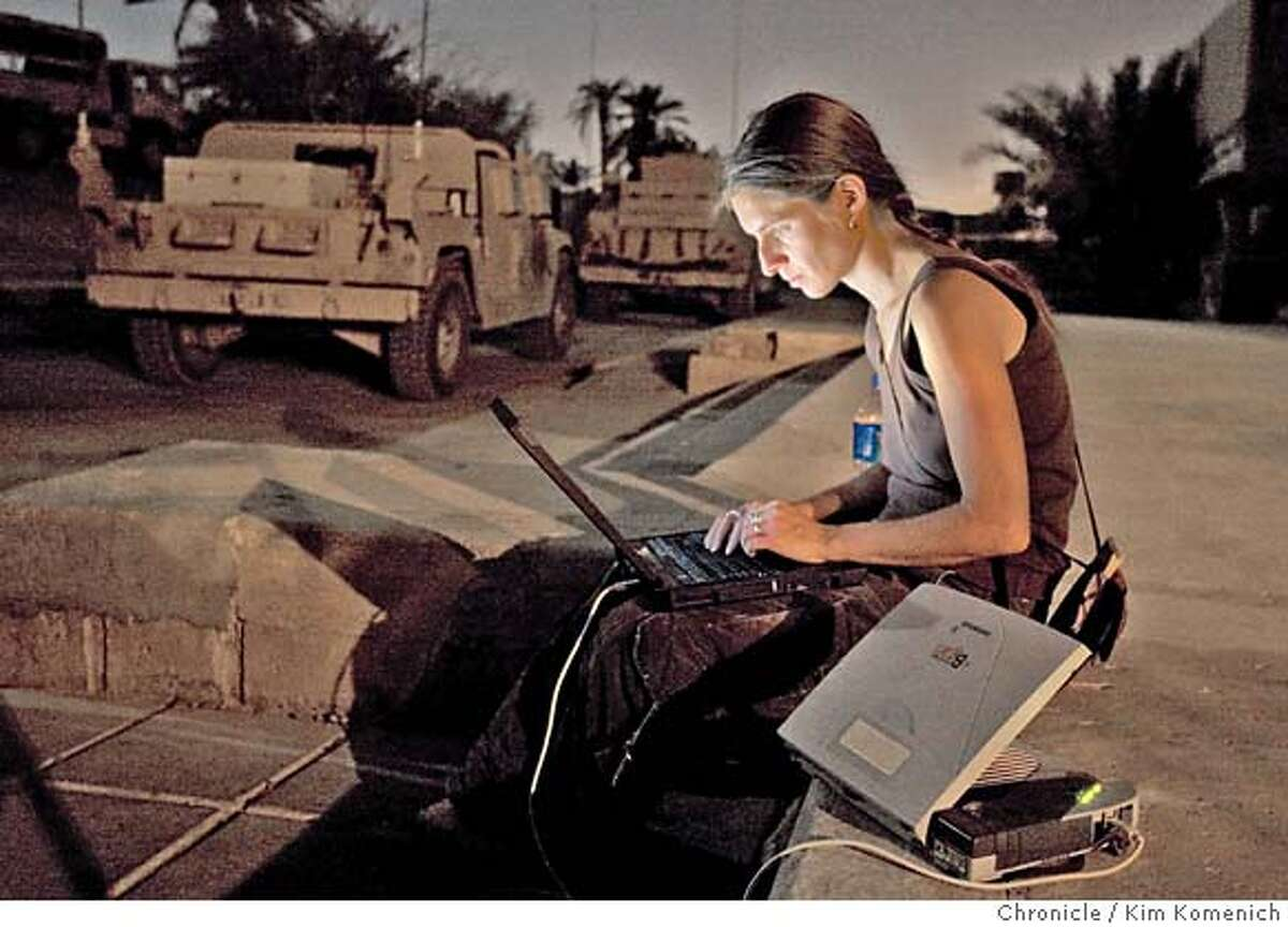 FOR GATE: BADKHEN BLOG: MORTAR Chronicle reporter Anna Badkhen sits on the steps of the 2-7 Infantry filing a story with her laptop and satellite modem. This photo to accompany blog on random mortar attacks around the building. San Francisco Chronicle photo by Kim Komenich