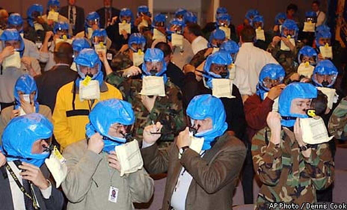 Pentagon military and civilian personnel take part in a training class Tuesday, Feb. 25, 2003, in the use of escape hoods to be used in case of a chemical, biological of nuclear attack. Some 80,000 gas masks will be available and officials will begin handing them out this week to 20,000 civilian and uniformed employees who work in the Pentagon headquarters, as well as some 3,000 to 4,000 others such as members of the press corps and staffs of shops, restaurants and the facilities in the building. (AP Photo/Dennis Cook)
