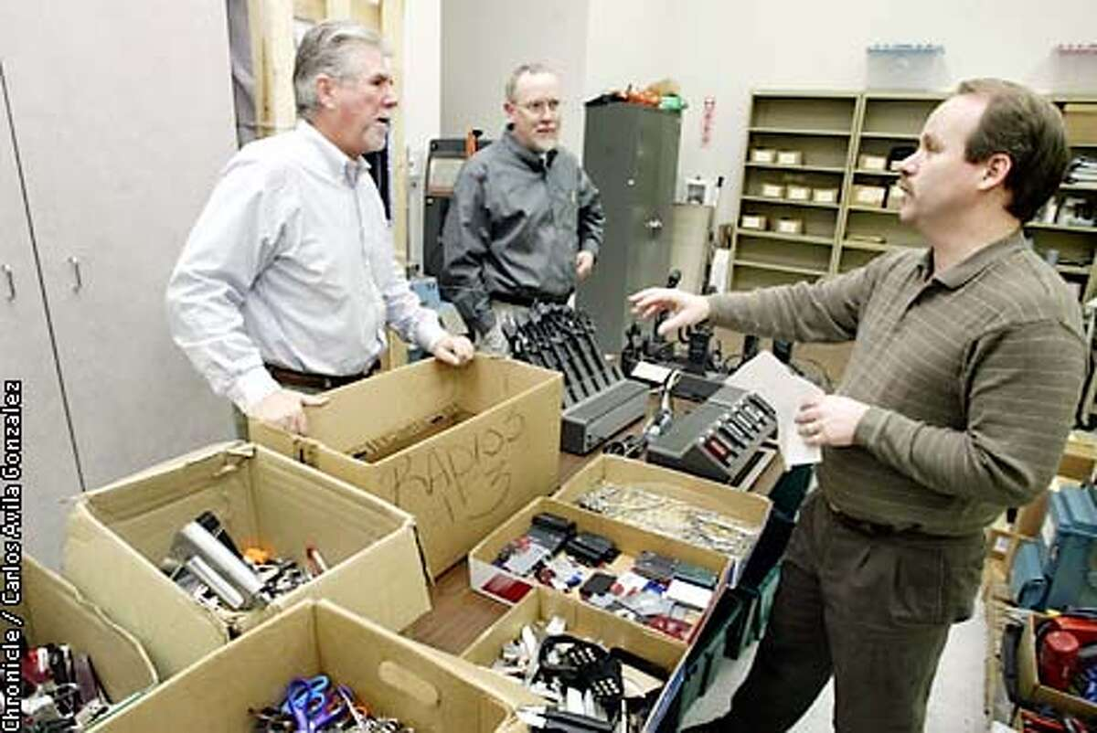 Mike Wilson, right, an associate materials analyst for the State of California Reuse Center, speaks with Robb Deignan, Director of Public Affairs, and Dan McDonough, the Manager of Property for the center, about confiscated airport items on Thursday, February 20, 2003. The items will be sorted and catalogued and auctioned off on Ebay. The state has been using EBay to sell surplus state items and confiscated material for several years. (BY CARLOS AVILA GONZALEZ/THE SAN FRANCISCO CHRONICLE)