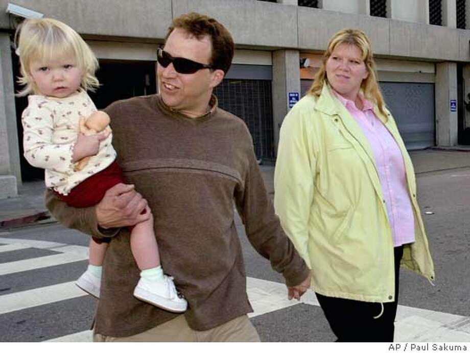 John Peterson, Scott Peterson's half brother, holds hands with his wife, Alison, right, as he holds his daughter, Katie, as they leave a Redwood City, Calif., courthouse, Thursday, Dec. 2, 2004 during the penalty phase of the trial. John and Alison Peterson testified on Thursday for the defense. Peterson is the Modesto, Calif., man who could be sentenced to death for the murder of his wife, Laci Peterson. (AP Photo/Paul Sakuma) Metro#Metro#Chronicle#12/3/2004#ALL#5star##0422496710 Photo: PAUL SAKUMA