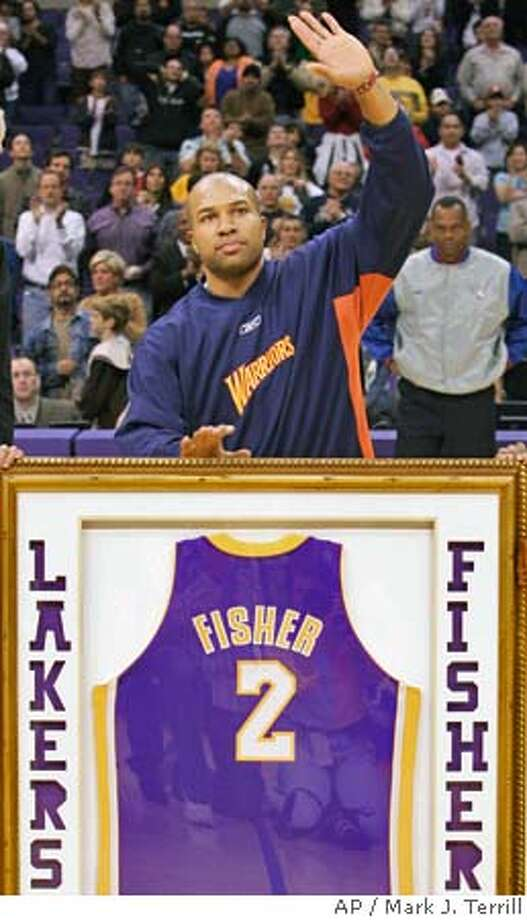 Golden State Warriors' Derek Fisher acknowledges the crowd as he receives a framed jersey for his years with the Los Angeles Lakers prior to their game, Friday night, Dec. 3, 2004, in Los Angeles. (AP Photo/Mark J. Terrill) Photo: MARK J. TERRILL