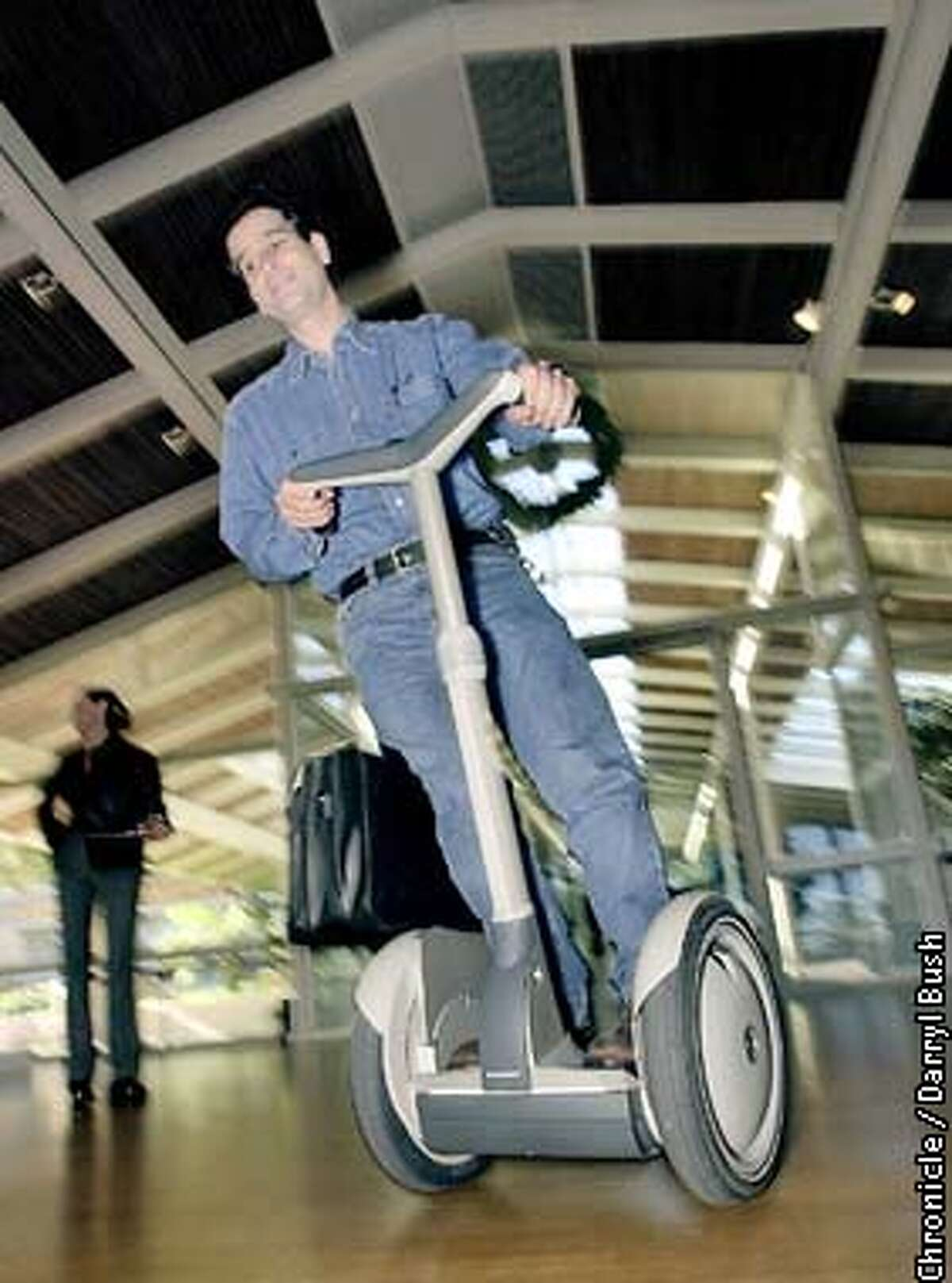 Inventor as well as CEO, Dean Kamen of Segway LLC, rides his Segway HT, the world's first dynamic self-balancing human transporter, around a room in Menlo Park. Chronicle Photo by Darryl Bush