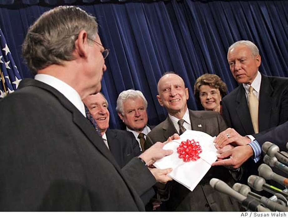 Rep. Mike Castle, R-Del., left, presents Senate members a copy of the house legislation, complete with a red bow, on Stem cells during a news conference on Capitol Hill, Wednesday, May 25, 2005. From left are, Castle, Sen. Tom Harkin, D-Iowa, Sen. Edward Kennedy, D-Mass., Sen. Arlen Specter, R-Pa., Sen. Dianne Feinstein, D-Calif., and Sen. Orrin Hatch, R-Utah. (AP Photo/Susan Walsh) Photo: SUSAN WALSH
