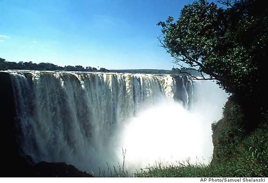Victoria Falls is shown from the Zimbabwe side in May, 1997. At over a mile wide and 343 feet high, it's easy to see why the local name, Mosi-oa-Tunya, translates into ``Smoke That Thunders.'' (AP Photo/Samuel Shelanski) MAGS OUT Photo: SAMUEL SHELANSKI