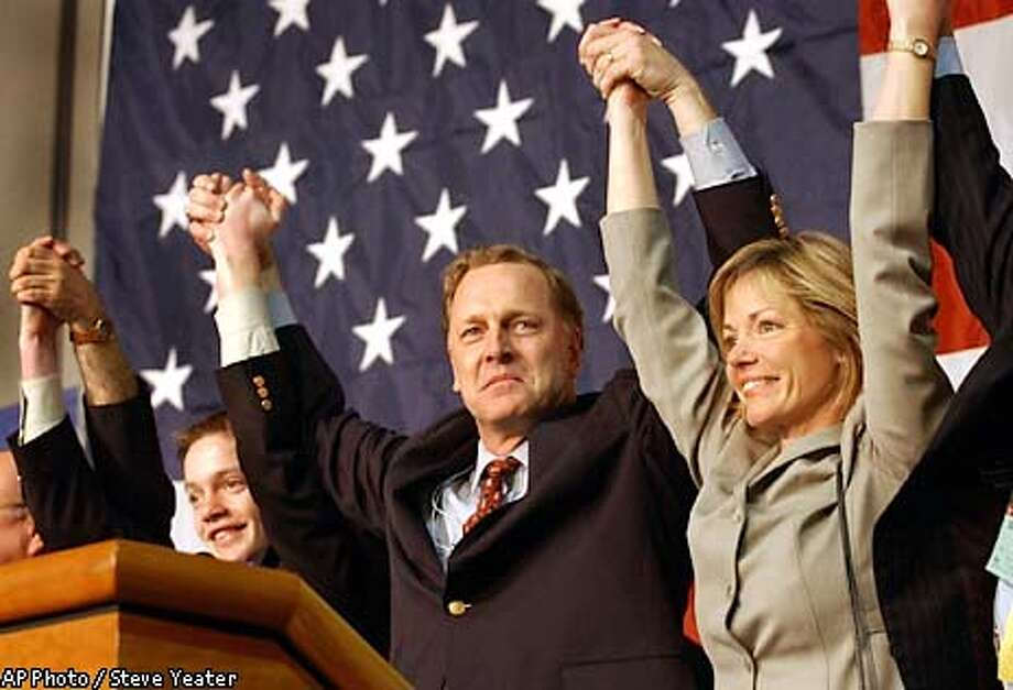 Palo Alto attorney Duf Sundheim, center, celebrates at the podium with his wife Sheryl, right, and son Eric, left, after being elected as the new party chairman during the Califorrnia Republican Party Convention in Sacramento, Calif., Sunday, Feb. 23, 2003. (AP Photo/Steve Yeater) Photo: STEVE YEATER