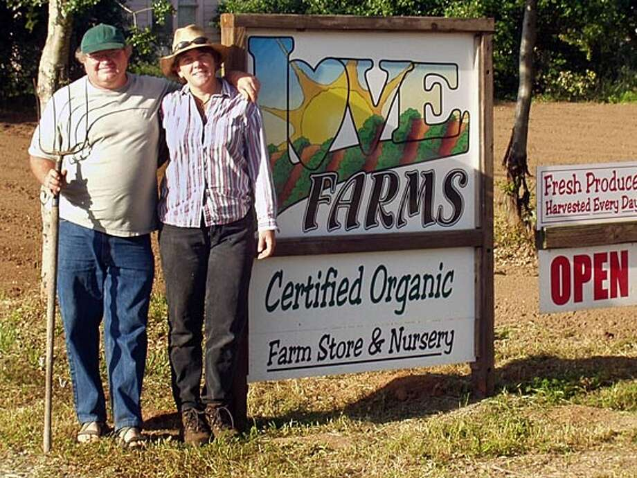Caption: Ron Love and Bibiana Goodrich in front of a sign for Love Farms.